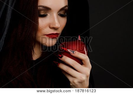 Stepmother witch gives poisoned red apple. Black background. horror fingernails