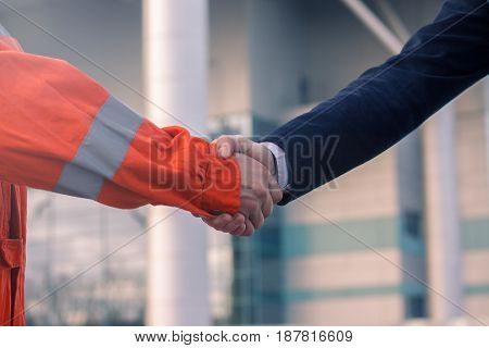 businessman handshaking with worker. Handshake of suit and boilersuit. Business modern background. Sunny day