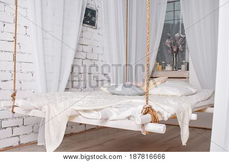 White loft interior with Hanging bed suspended from the ceiling. Modern design