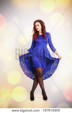 beautiful brunette in a blue dress dancing
