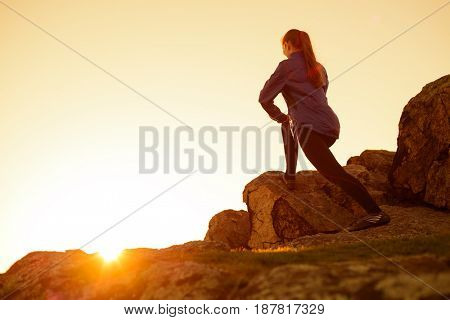 Young Fitness Woman Stretching her Legs in the Mountains at Sunset. Female Runner Doing Stretches Outdoor. Healthy Lifestyle Concept.