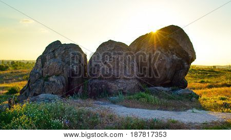 Beautiful Evening Landscape with Big Rocks in the Field at Sunset