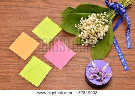 Flower of the Valley and paper for notes on the wooden table top