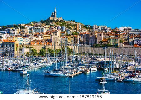 Marseille in May. The water area of the Old Port - yachts, speedboats and fishing boats. On the hill - splendid Basilica of Notre-Dame de la Garde
