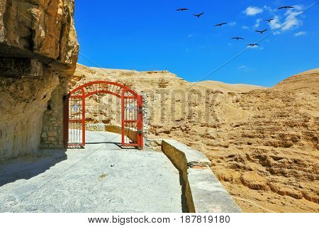 Decorative red gate with a cross on a mountain road going to the temple. Wadi Kelt near Jerusalem