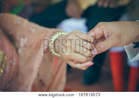 picture of man and woman with wedding ring in Thai weeding vintage style
