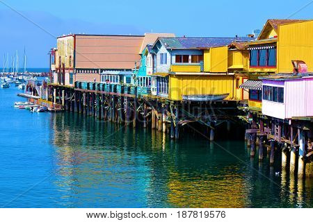 Monterey Bay Warf with colorful buildings which hosts retail stores and restaurants taken in Monterey, CA