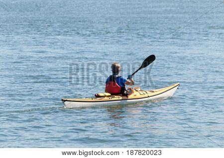Lone kayak with older female paddling in open water away from viewer