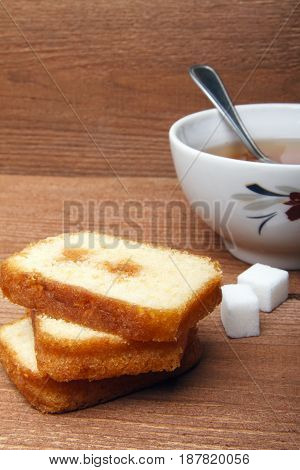 Black tea with sugar and cake with jam on wooden background. There is room for text
