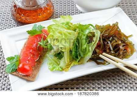 Asian dietic salad with Laminaria served on white dish