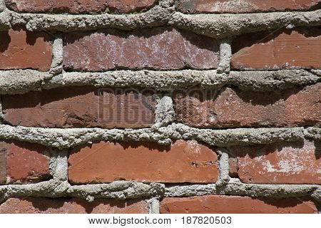 Close up of an old red brick and mortar wall beautifully textured by time