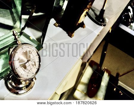 Time Management Concept Decorative Table Clock in Globe Shape with World Map in Side on A Cabinet.