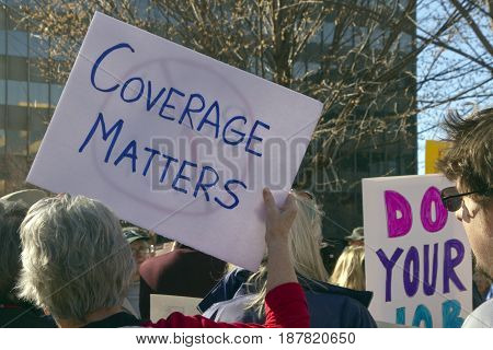 Asheville North Carolina USA - February 25 2017: Protesters hold signs at an Affordable Care Act rally saying that coverage matters as Republicans move to repeal Obamacare on February 25 2017 in Asheville NC