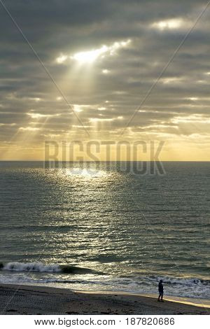 Light rays break through dark clounds and pour down upon a calm sea creating a luminous circle of light out as a lone man pensievely walks the beach
