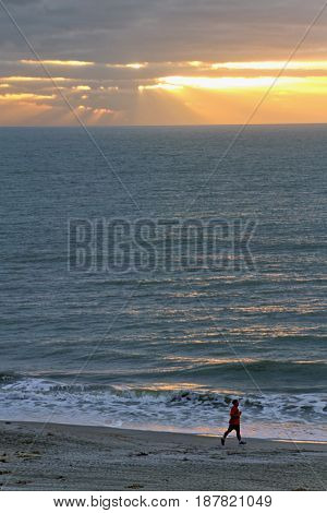 Golden light rays break through dark clounds to pour down upon a shimmering sea a lone man runs along the beach