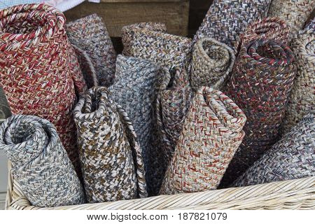 A bunch of multicolored rugs rolled up together in a large basket