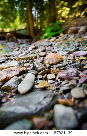 Colorful stones stacked along the shore edge in Glacier National Park Montana