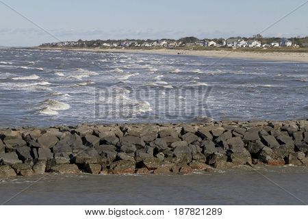 Rock jetty with a lower level of less turulent water on one side and higher choppy waters on the other side with a distant beach and houses behind it