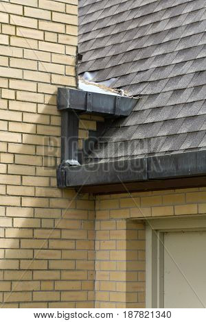 Artistic textures of shingles and bricks where a roof wall drain pipe and doorway meet