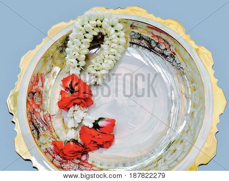 Beautiful Jasmine Garland with Red Roses Blossoms on Porcelain Pedestal Dish The Garland in Thai Tradition Style.