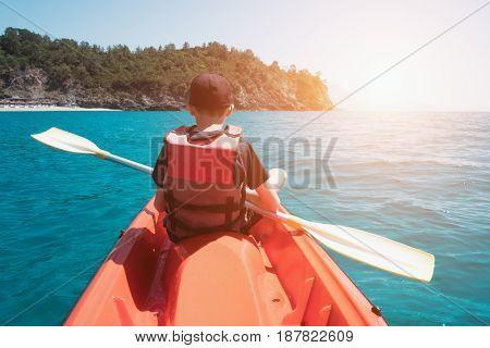 Boy in life jacket on orange kayak. Sunny day on mediterranean sea. Summer time