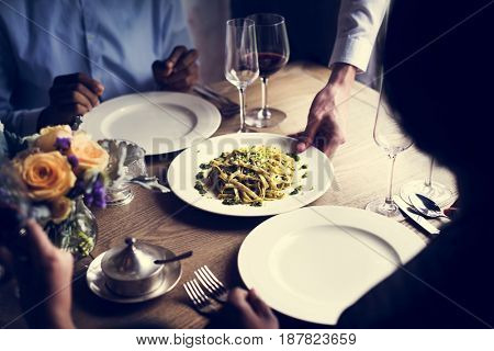 Waiter serving pasta meal to the customers