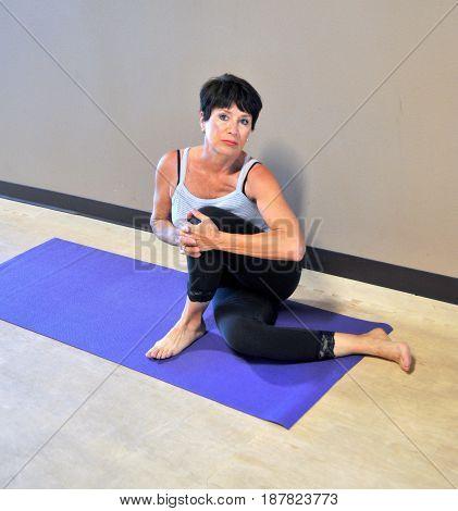 Mature female beauty doing yoga exercises inside a healthclub.