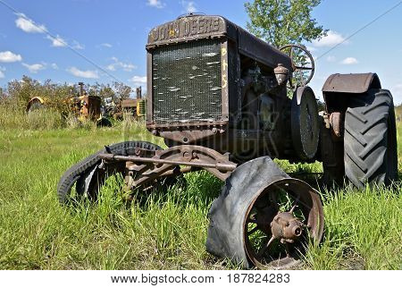 BARNESVILLE, MINNESOTA, September 14, 2014: The worn out old John Deere tractor is a product of John Deere Co, an American corporation that manufactures agricultural, construction, forestry machinery, diesel engines, and drivetrains.