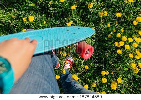 Bright and colorful skateboard in a hand of a young woman
