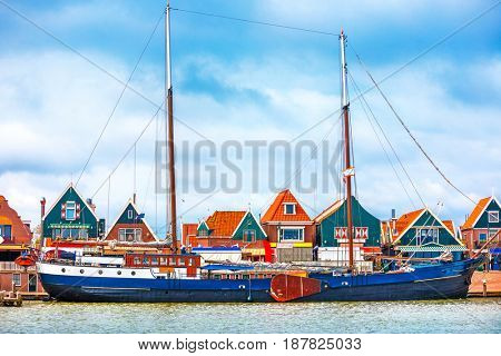 Fishing village Volendam panoramic view Holland Netherlands with antique ship small wooden houses on coast lake Markermeer sunny day blue sky clouds.