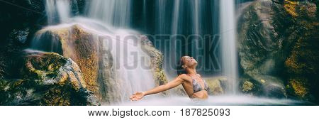 Spa and wellness waterfall woman carefree banner. Happiness woman relaxing in water with arms up raised in freedom. Health and relaxation. Waterfall bikini girl landscape panorama crop.