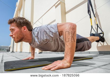 Fitness man doing pushups using suspension straps at fitness centre. Athlete doing bodyweight push-up exercises on floor outdoors.