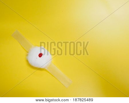 Close-up detail of a cotton ball and tape dressing from with blood stains previously used for phlebotomy on a yellow shiny background. Healthcare and medicine concept.