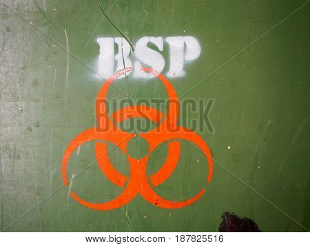 Close-up detail of an orange biohazard symbol painted onto the side of a green medical waste disposal dumpster with many scratch marks on the plastic. Hazardous waste and science concept.