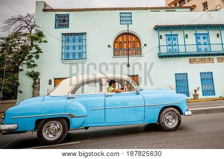 Old blue American car driving urban Cuban capital city