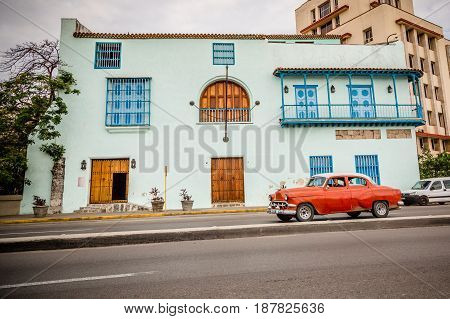 Old red American car driving urban Cuban capital city