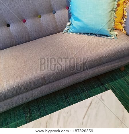 Gray sofa with blue and yellow cushions. Living room detail.