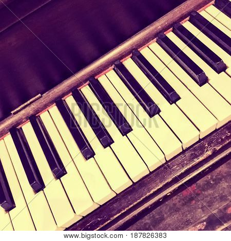Keyboard of an old piano. Retro style photo.