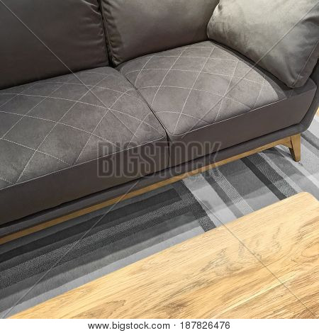 Comfortable gray sofa and wooden coffee table. Modern style furniture.