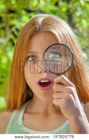 surprised child with magnify glass looking