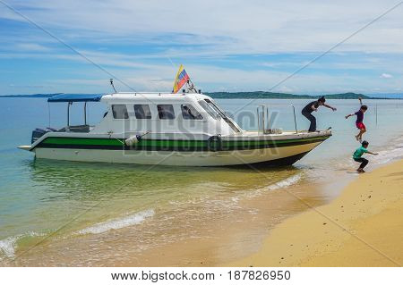 Labuan,Malaysia-Feb 19,2017:Kids jumping off the boat into a beautiful sandy beach of Papan island in Labuan,Malaysia.Having fun on a summer vacation at the beach with friends