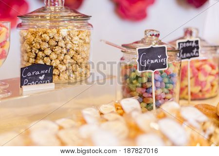 Colorful Candies In Jars On A Dessert Table With Donuts, Cookies And Popcorn.