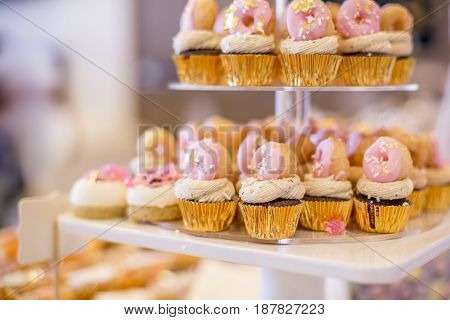 Mini Chocolate Cupcakes Topped With Mini Pink Donuts On A Dessert Table.