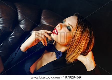 Young attractive girl in a jacket and bow tie. Femme fatale. Evening makeup smokey eye. Passion and desire.