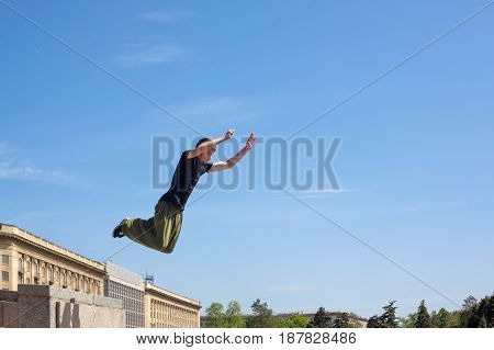 A young man is jumping from the wall. Parkour in the urban space. Sports in the city. Sport activity.