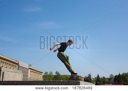 Young man jumps on the wall. Parkour in the urban space. Sports in the city. Sport activity.