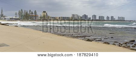 Panorama of Sunshine Coast foreshore at Alexandra Headlands Mooloolaba with surf sand rocky seafront and cloudy sky