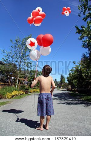 Young boy outside in summer with Canada day, maple leaf flag birthday balloons.