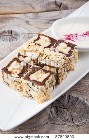 Chocolate rolls with almonds served with white cream