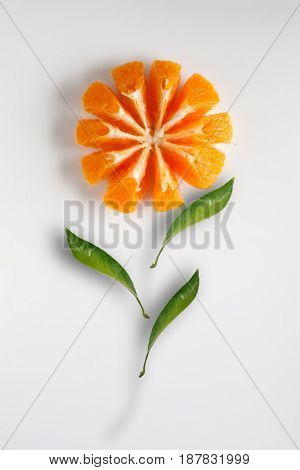 Image of orange cut and shaped as flower with leaves on white background